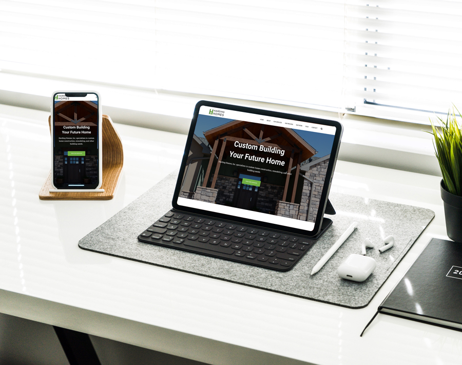 computer and phone on table showing Harding Homes website