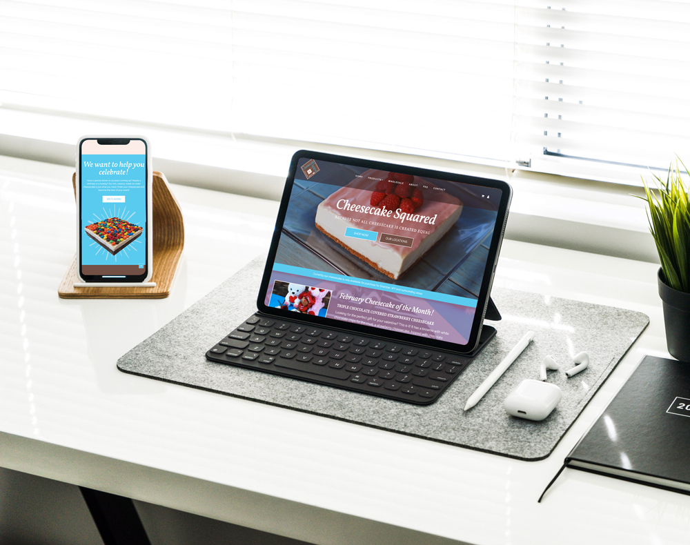 Computer and phone on table showing Cheesecake Squared website